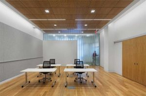 A furnished multipurpose room supporting group training in the Staten Island Family Justice Center quickly resets as a conference room, presentation venue, or event space by using tables on casters and stacking chairs.