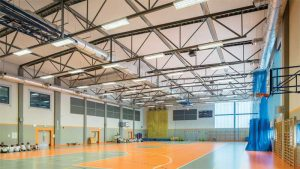 In activity rooms such as gymnasiums, the acoustic goal is to prevent excessive loudness. The design aims to ensure announcements are understandable. Acoustic treatment often needs to have abuse-resistant surfaces and be up high where they are less likely to get damaged. Photo courtesy Bartosz Makowski