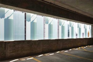 The translucent white laminated glass filters gentle, diffused daylight into the parking structure.