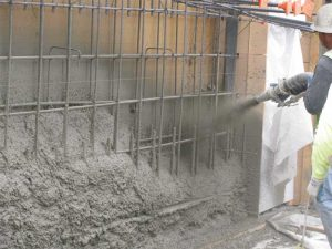 Shotcrete being applied to form a structural reinforced blind-side wall.