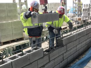 Electric-powered lift-assist devices are capable of hoisting up to 61 kg (135 lb), allowing masons to lift, move, and place blocks with ease.