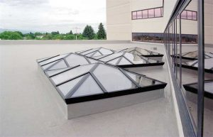 These skylights are a good example of a high-quality installation in a challenging location. The American Society of Civil Engineers/Structural Engineering Institute (ASCE/SEI) 7, Minimum Design Loads for Buildings and Other Structures, provides formulas for calculating the resulting dead, wind, snow, and other loads acting on the skylights, as does Chapter 24 of the International Building Code (IBC). The area between the wall and the skylight is especially difficult due to the possibility of drifting snow that must be accounted for in the design. Photo courtesy CrystaLite
