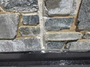 The wall panels at areas of leakage relied on the secondary seal at the face of the stone veneer to prevent water from entering the building. Water bypassed the secondary seal and entered the building due to the lack of a primary seal at architectural precast concrete (APC) panel joints. Photo © Jeffrey N. Sutterlin, PE