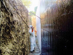 Spray installation of polymerized asphaltic emulsion.
