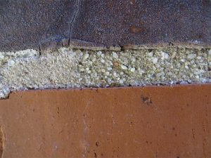A close-up view shows the variation in size and color of sand aggregate in the existing pointing mortar.