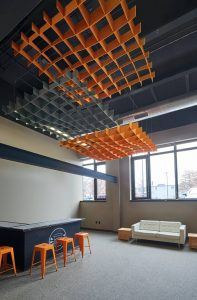 Three 2.4 x 2.4-m (8 x 8-ft) open cell felt clouds were installed to reduce reverberation time and provide spot acoustics over the student-run coffee bar at Stone Independent School. The clouds are installed in layers to obtain more acoustical performance.