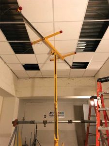Figure 1: Following the baseline test of just the concrete floor slab (metal deck flutes visible through open parts of ceiling) a standard, metal, tee-bar, suspension grid, and ceiling panels were installed (in process).