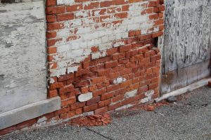 The exterior brick masonry near the base of this multi-wythe wall has deteriorated due to moisture intrusion, and the presence of non-breathable coatings limited the release of moisture. Photo © Kenneth Itle, WJE